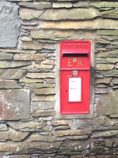 Red post box in dry stone wall