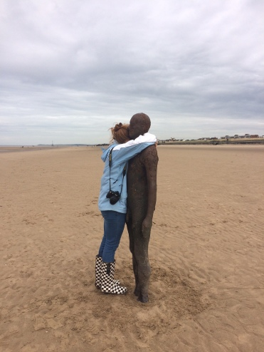 Lucy (my daughter) gives one of Antony Gormley's statues a hug