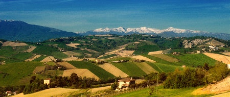 The snow-capped Sibillini Mountains rise above the rolling hills of Le Marche