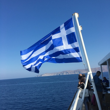 The Greek flag billows in the wind