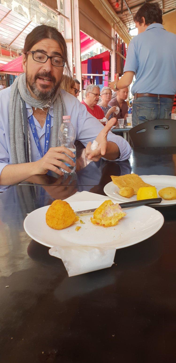 Giorgio explains the respective virtues of arancini - street market tour, Palermo, Sicily
