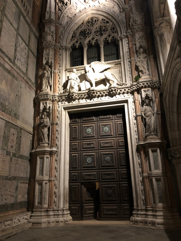 Porta della Carta - the winged lion of St Mark dominates this huge, timber door - originally the entrance to the Doge's Palace, Venice. St Mark's Basilica to the left.