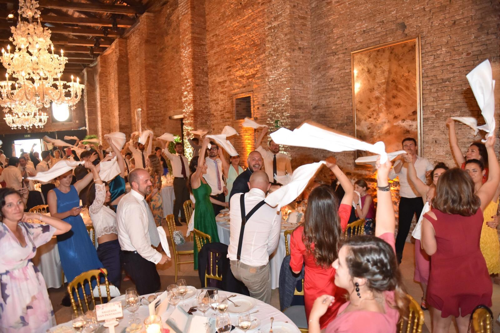 Guests singing and waving their napkins, Napoli style at Giulia and Carlo's wedding. Photo: Mirco Toffolo.